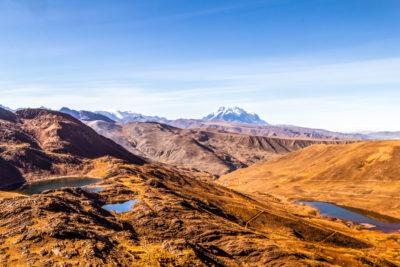 Bolivien: der Altiplano bei La Pz/ El Alto.  Rechts einer der vielen Wasserspeicher. Im Hintergrund der schneebedeckte Inti Illimani.