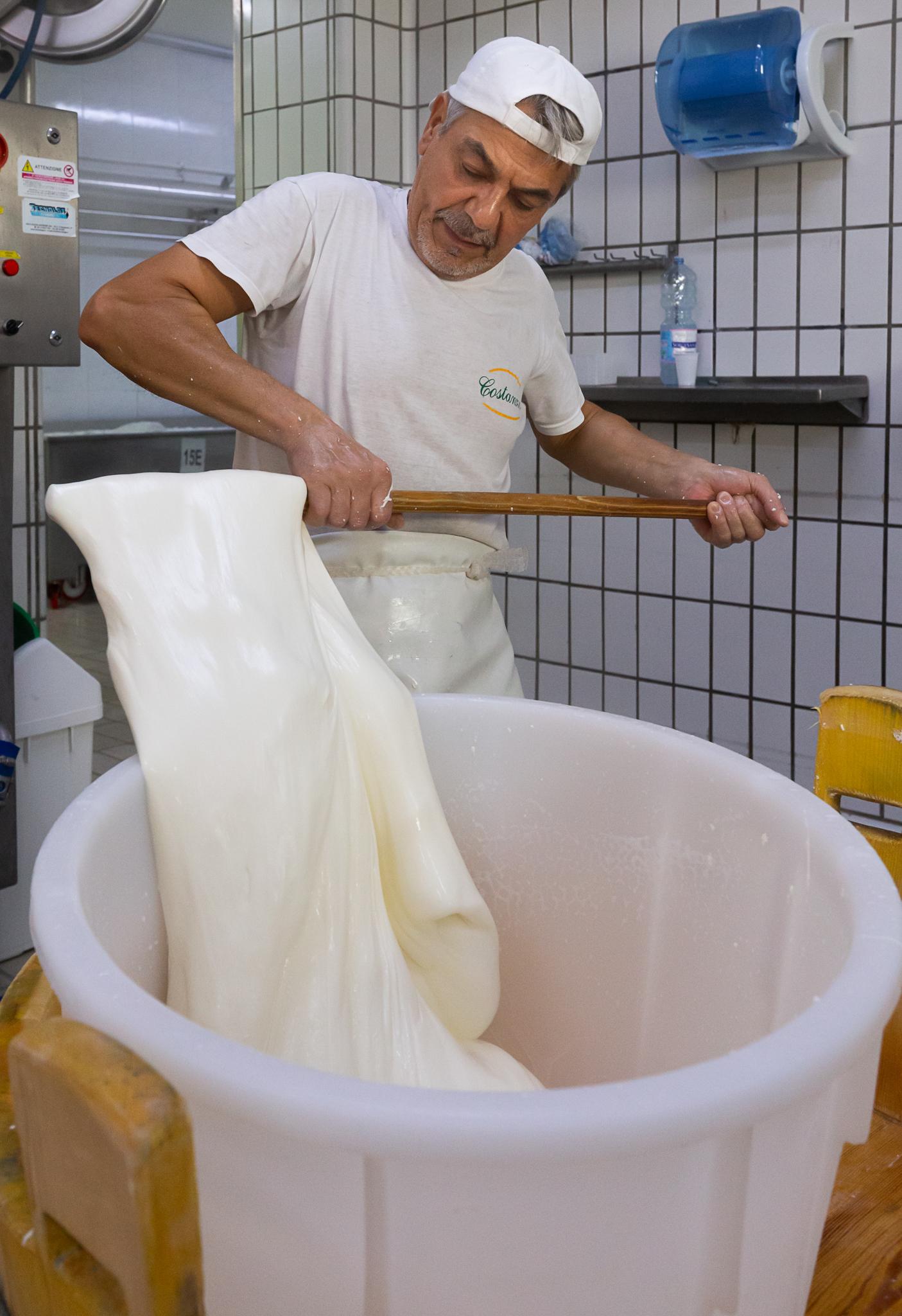 Pasquale, Käser im Caseificio Costanzo, zieht Käsemasse für den Büffelmozzarella.